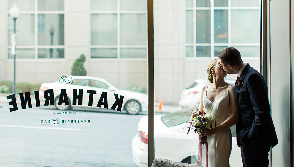 bride and groom kissing inside restaurant next to glass window with restaurant logo